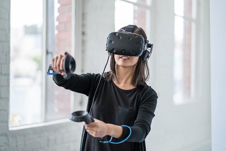 Junge Frau spielt mit der HTC Vive